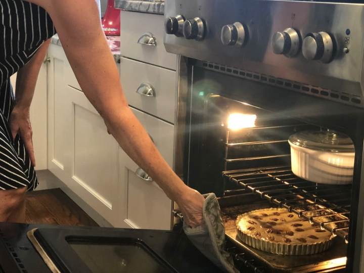 Putting the Sweet Potato Pecan Pie in the oven. Using a cookie sheet prevents spillover messes in the oven.